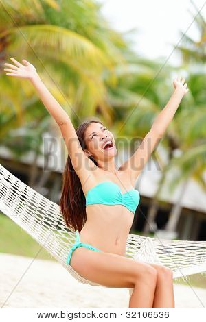 Vacation woman on beach happy and joyful with arms raised sitting in hammock. Beautiful young bikini model in summer holidays resort. Mixed race Caucasian / Chinese Asian woman.