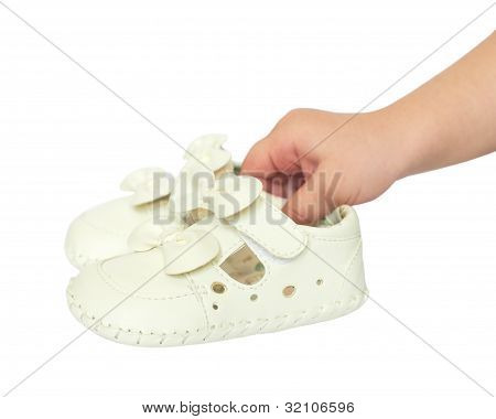 Kids  Hand Holds Small White Baby Shoes, Studio Shoot Isolated