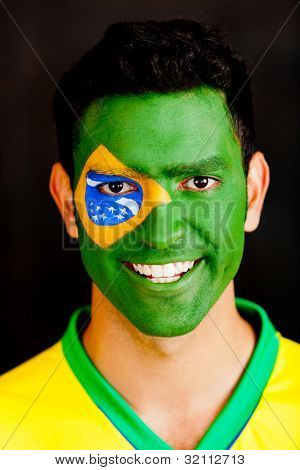 Brazilian man with flag painted on his face - isolated over a black background