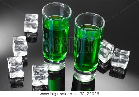 Two glasses of absinthe and ice on grey background