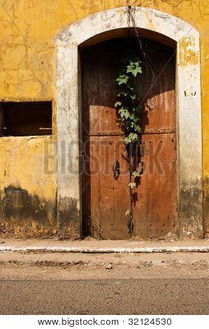 Old Brown Locked Door In Yellow House