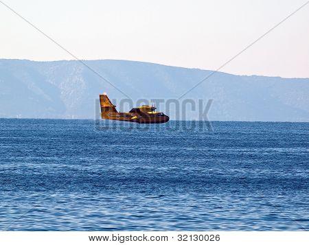 Yellow airplane flying near sea
