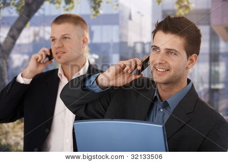 Smiling businessmen making phone call outside of office building.