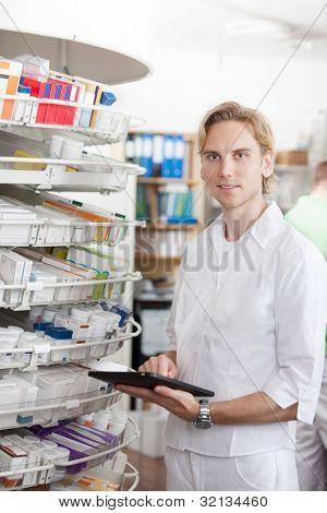 Retrato de sonriente hombre farmacéutico con Tablet Pc en farmacia.