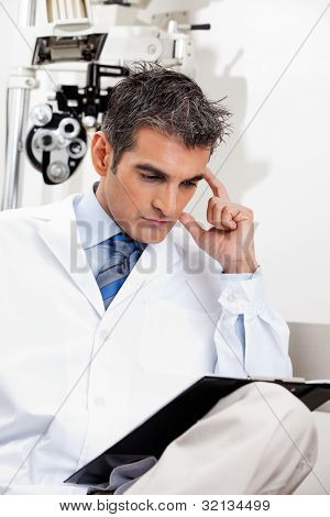 Serious male optometrist reading a document with concentration at his clinic