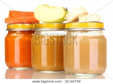Jars of baby puree with spoon isolated on white
