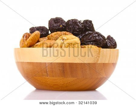 yummy dried plums and figs in wooden bowl isolated on white