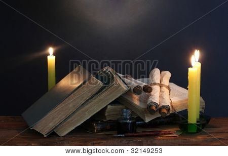 old books, scrolls, feather pen inkwell and candles on wooden table on blue background