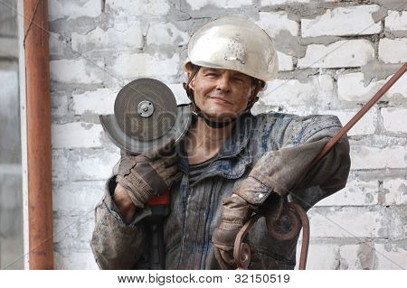 Man with angular electric grinder. Ukraine