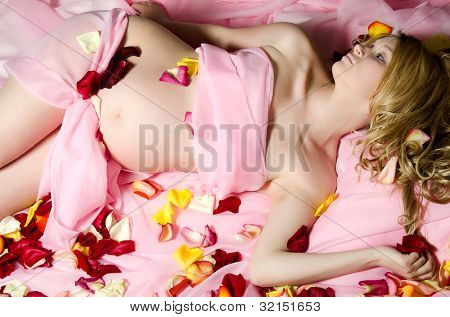 The pregnant woman On a pink coverlet