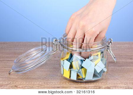 Mano arrojando papel de lotería en mesa de madera sobre fondo azul