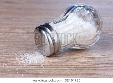 Glass saltcellar with salt on wooden background