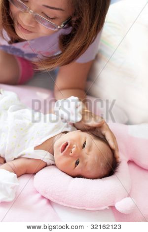 woman and infant sleep on baby bed
