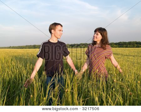 Young Couple Walking Field Holding Hands