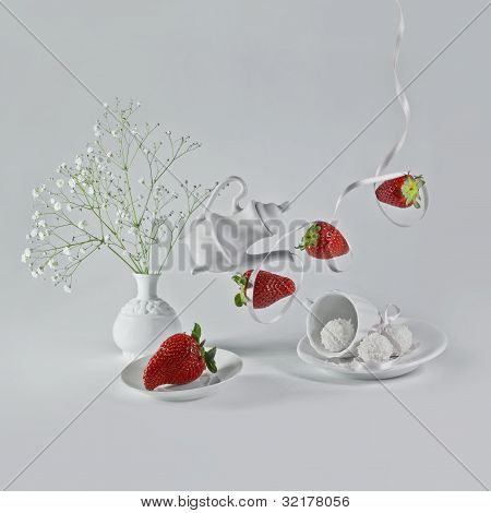 Flying strawberries with white ribbon and decorative dishes.
