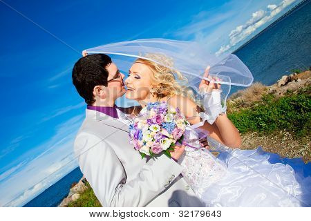 Tender Kiss Of Happy Groom And Bride On A Sea Coast