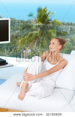 Beautiful happy woman sitting barefoot on a white sofa in her living-room with a tropical view through the large glass window