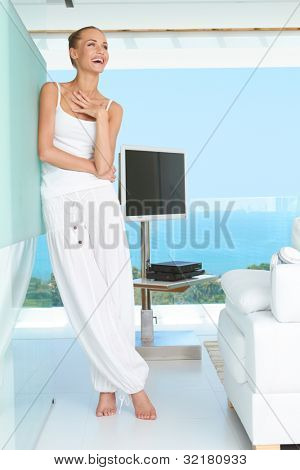Woman standing laughing in casual white outfit in a modern glass fronted living room with a view of the ocean