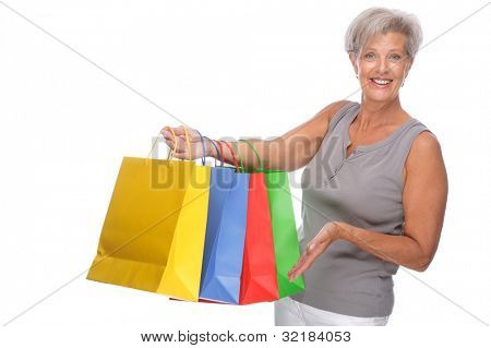 Full isolated portrait of a senior woman with shopping bags