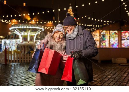 poster of sale, winter holidays and people concept - happy senior couple with shopping bags at christmas marke