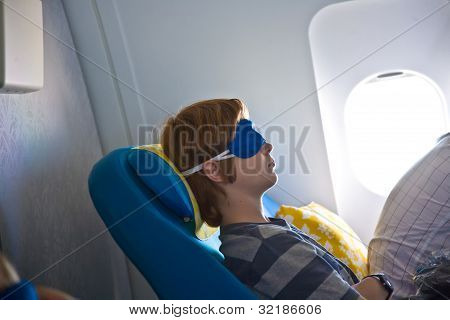 Young Passenger Sleeping In The Aircraft