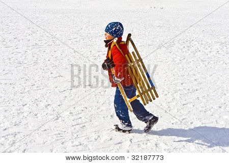 child carrying his sledge in snowy landscape