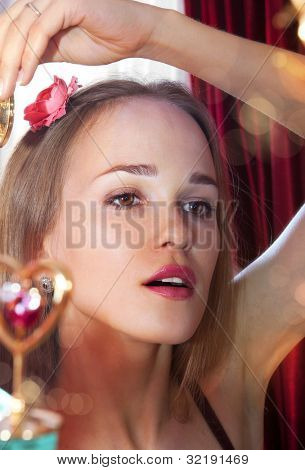 beautiful girl smartens up in front of mirror