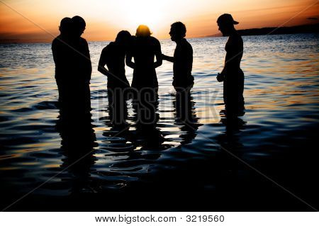 Beach Sunset With Young Men In Water