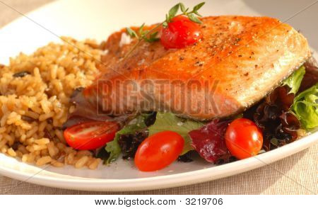 Piece Of Seared Salmon On A Bed Of Greens With Tomatoes And Brown Rice