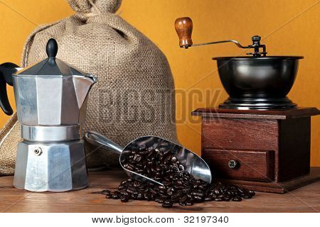 Still life photo of a  caffettiera or moka pot with traditional coffee grinder hessian sack and arabica beans in a scoop.