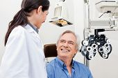stock photo of cataract  - Smiling mature patient consulting with optometrist for an eye checkup - JPG