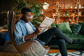 Black man reading newspaper in a comfortable chair poster