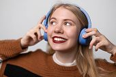 Young Pretty Blonde Girl With Lips Painted Bright Red Lipstick, Long Hair And Blue Eyes Enjoys Music poster