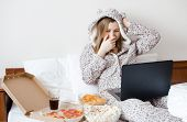 Beautiful Young Woman Eating Unhealthy Food And Crying. Caucasian Teenage Girl In Cute Warm Pajamas  poster