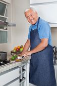 Portrait of smiling senior man cutting vegetables at kitchen counter