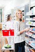 Portrait of female customer standing near shelf at drugstore holding medicine