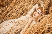 Romantic young woman with beautiful red hair lies on a wheat field. Beauty, fashion. Modern hippie,  poster