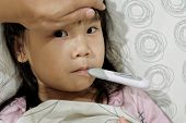 Asian Child Girl Is Sick And Has A Thermometer In Her Mouth While Lying On The Bed. Mother Checking  poster