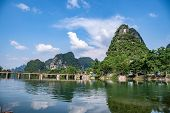 River Landscape And Picturesque Yangshuo Village With Green Mountain Ranges. Guilin, China. poster