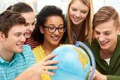education, travel and geography concept - happy high school students or friends looking at earth glo poster