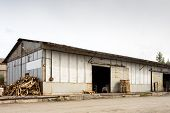 A Large Metal Industrial Warehouse For Storing Goods, Next To It Are Wooden Pallets For Storing Good poster