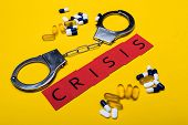 Illegal Drug Crisis Concept Showing Pills And Handcuffs With The Message Crisis On A Yellow Backgrou poster