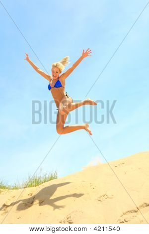 Girl Jumping Off A Sand Dune