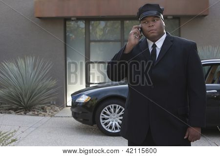 Mixed race chauffeur standing by luxury car holding telephone
