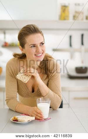 Young Woman Eating Snacks In Modern Kitchen And Looking On Copy