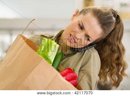 Concerned Young Housewife With Big Shopping Bag Talking Mobile P