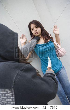 Um ladrão agressivo segurando o pescoço da mulher, ameaçando-a com a faca
