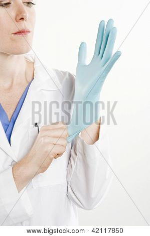 Female doctor wearing sterilized hand glove isolated over white background