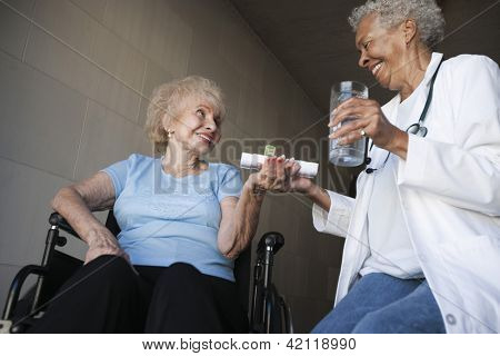 Low  view of African American female doctor giving medication to an elderly patient