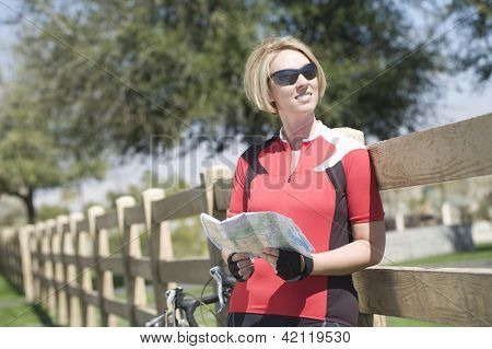 Happy female bicyclist holding road map while leaning on fence in park